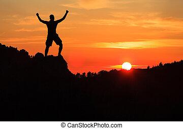 Man hiking climbing silhouette in sunset mountains