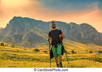 Young man with nordic sticks hiking at dusk in Apuseni Mountains in Transylvania, Romania.