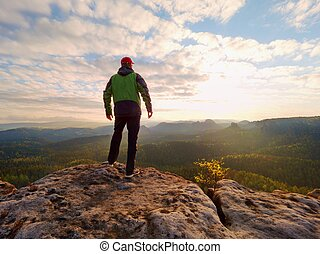 Man hiking in mountains, watching sunset and horizon over beautiful landscape.