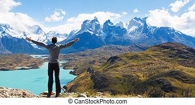 man hiking in patagonia - man at mirador condor enjoying...