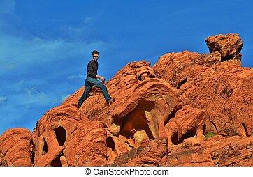 Man hiking on some red rocks