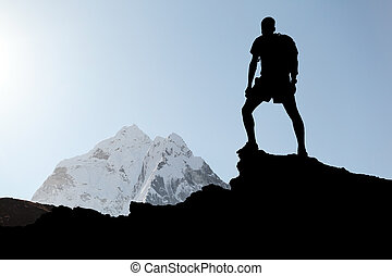 Man hiking silhouette in Himalaya mountains. Male hiker with backpack on top of mountain looking at beautiful night Mount Ama Dablam in Himalayas, Nepal