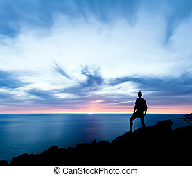 Man hiking silhouette in mountains, sunset and ocean. Male hiker with backpack on top of mountain looking at beautiful night landscape.