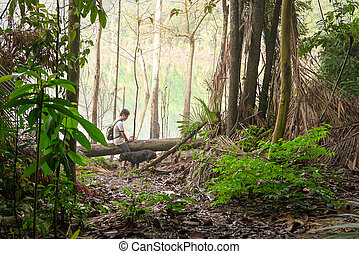 Man hiking with his dog in a tropical jungle