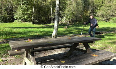 Man hiking with poles in wood on fall and eating snack,...