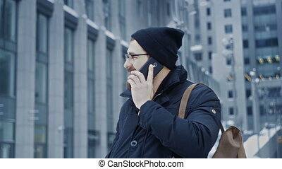 Man hipster talking on phone in front of office center