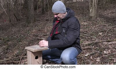 Man hit nail into the birdhouse and show thumb up