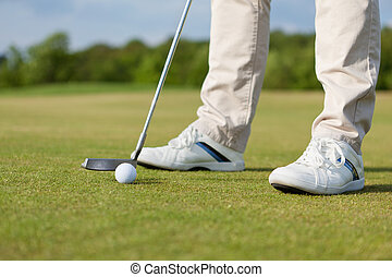 Man Hitting Golf Club With Ball On Course - Low section of...