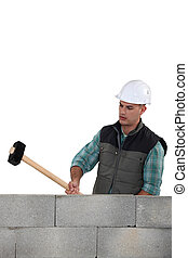 Man hitting wall with sledge-hammer