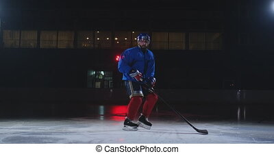Man hockey player in hockey uniform leaves with a stick in...