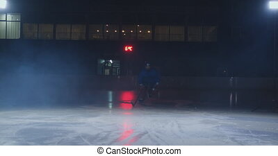 Man hockey player with a puck on the ice arena shows...