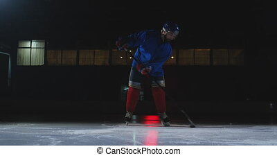 Man hockey player with a puck on the ice in hockey form...