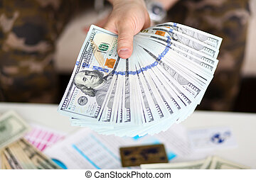 Man hold in hand big fat pack of US money