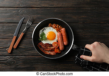 Man hold pan with fried eggs on wooden background, top view