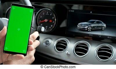 Man hold smartphone in car on dashboard background - Modern...