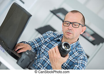 man holding a camera and typing on the laptop
