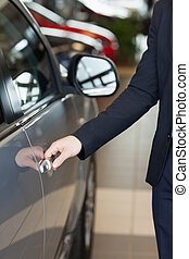 Man holding a car door handles in a car dealership