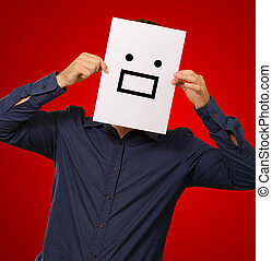 Man holding a card with face paper