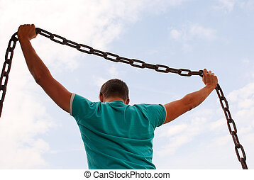 Man holding a chain against blue sky