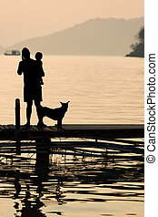 Man holding a child on wooden Pier during sunset with pet, Family scene
