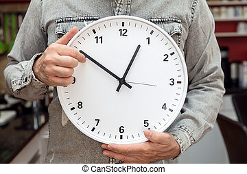 man holding a clock, concept time change