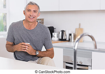 Man holding a cup in the kitchen