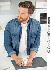 man holding a cup of coffee in the kitchen