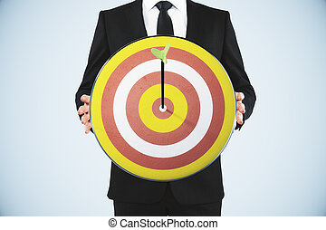 Man holding a dart board with a direct hit on target