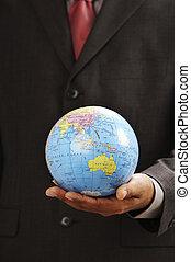 man holding a desk globe on the palm