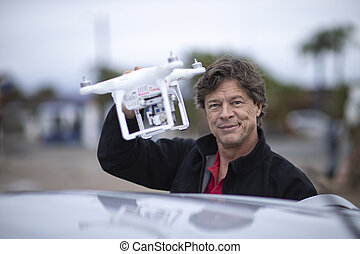 Man holding a drone with his hand.