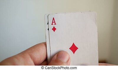 man holding a game in the casino poker card combination of three aces