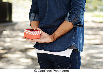 Man holding a gift box behind his back.