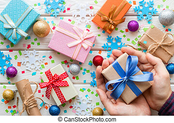 man holding a gift box on the background of Christmas decorations