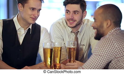Man holding a glass of beer in hand while sitting at the bar