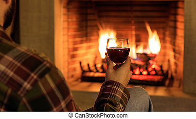 Man holding a glass of red wine on burning fireplace background