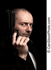 Man holding a gun - Portrait of a handsome man holding a...