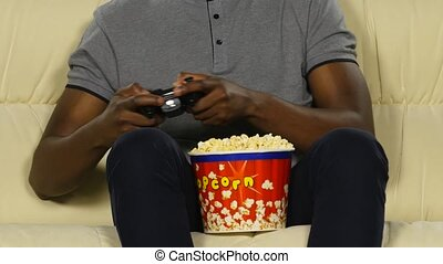 Man holding a joystick and eating popcorn - Male hands...