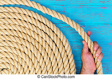 Close up background shot of the hand of a man or mariner holding a loop of a neatly coiled new rope over a turquoise blue crackle paint wooden panel in a conceptual image