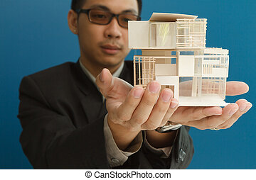 Man holding a model of a house in his hands.