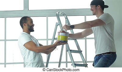 Man holding a paint can while his friend standing in the background