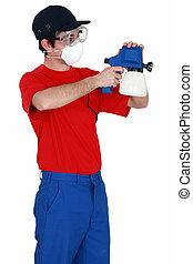 Man holding a paint sprayer