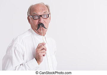 Man holding a paper moustache - Portrait of a elderly man...