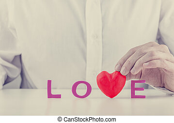 Man holding a red heart in the word - Love