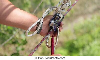 Man holding a rope and catches carabiner.