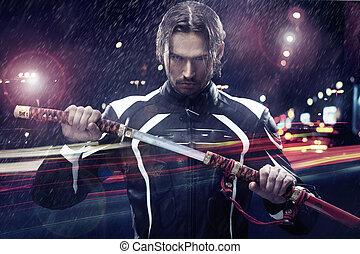 Man holding a samurai sword on a night city street