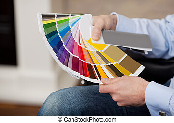 Man holding a set of paint colour swatches in all the ...