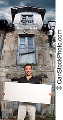 Man holding a sign by a old house
