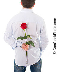 man holding a single red rose behind his back