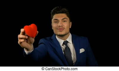 Man holding a small red heart on valentine day