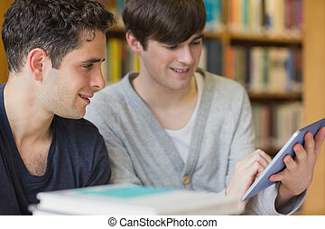 Man holding a tablet PC at the library smiling